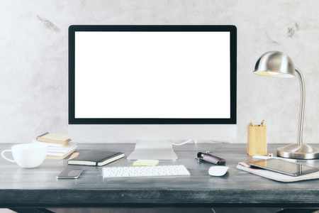 Creative desktop with blank white computer screen and other itmes. Mock up