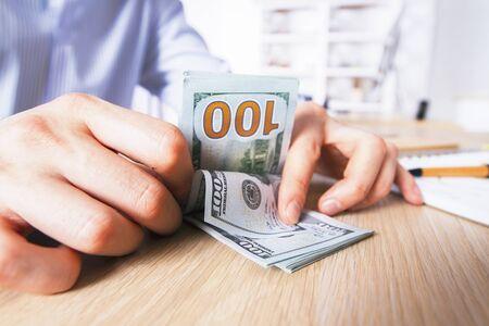 apilar: manos masculinas que cuentan billetes de dólar en el escritorio de madera clara
