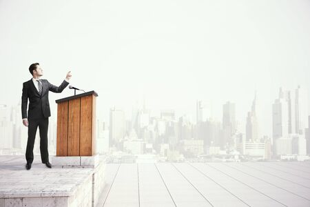 motivational: Caucasian businessman in black suit speaking from tribune on foggy city background