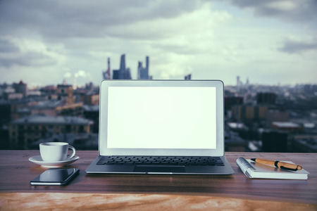 Wooden desktop with blank white laptop, phone, coffee cup and notepad with pen on city background. Mock up Stock Photo