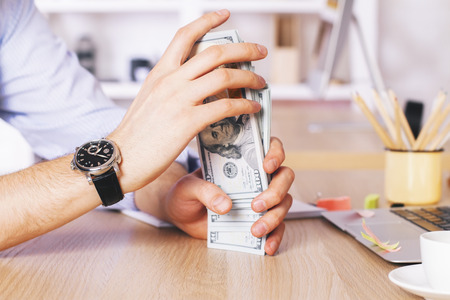 sorting out: Male hands sorting out dollar stack at wooden table in office Stock Photo