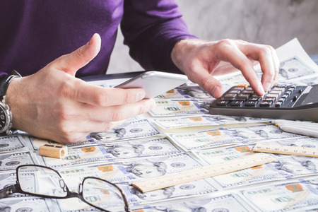 estimating: Closeup of man using phone and calculator on wooden table covered with dollar banknotes
