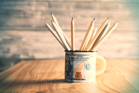 front view: Dollar print mug with pencils on wooden table