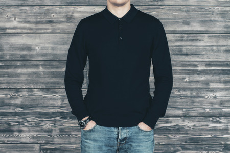 pocket: Caucasian man in black shirt and jeans standing in front of wooden wall. Mock up Stock Photo