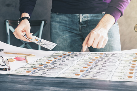 sorting: Businessman sorting out dollar banknote rows on wooden table Stock Photo