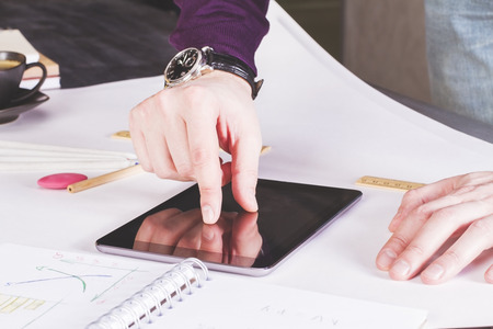 zooming: Male hand zooming in on tablet placed on large whatman with office tools