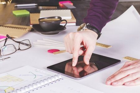 zooming: Male hand zooming out on tablet placed on large whatman with office tools Stock Photo