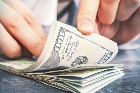 letra de cambio: Primer de las manos masculinas que cuentan billetes de cien dólares sobre la mesa de madera Darl