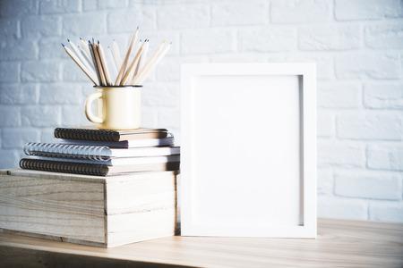 Bureau met leeg fotolijstje en potloden in ijzer mok geplaatst op boeken en houten doos. Mock up Stockfoto