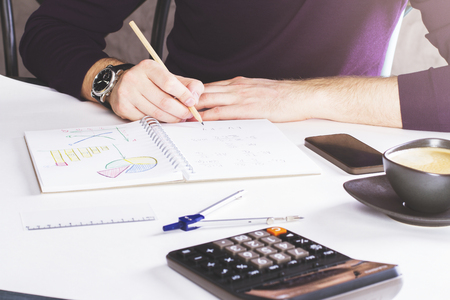 schemes: Man drawing business schemes in copybook on white surface with calculator and some other items
