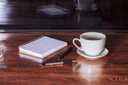 Tavolo con tazza di caffè, blocco note e due penne