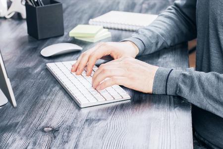 klawiatury: Boczne pulpit z męskich rąk pisania na klawiaturze, monitorze komputera i narzędzi biurowych