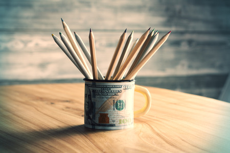 sideview: Sideview of dollar print mug with pencils on wooden table