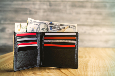 Open black wallet wth dollars and plastic cards on wooden table