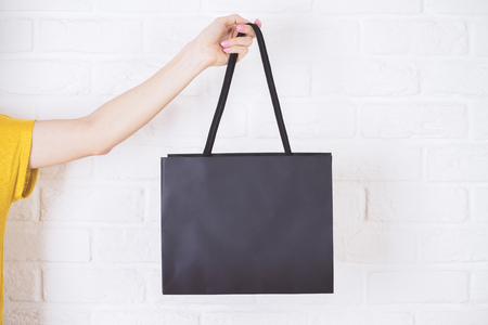 Close-up van vrouwelijke hand die zwarte boodschappentas op witte bakstenen achtergrond houdt. Stockfoto