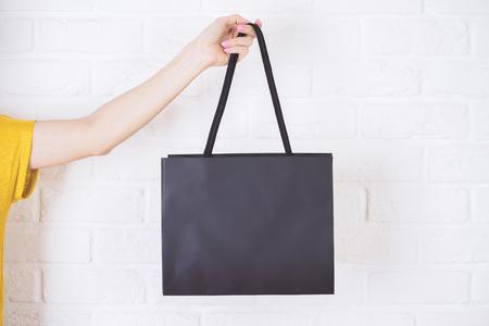 Primer plano de la mano femenina que sostiene el bolso de compras negro sobre fondo blanco de ladrillo.