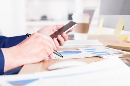 sideview: Sideview of businessman using cellphone over business charts in office Stock Photo