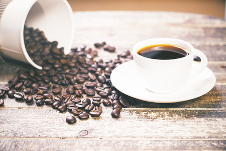 falling out: Coffee beans falling out of coffee cup on wooden desktop