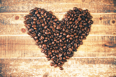 grano de cafe: Corazón del grano de café en la superficie de madera