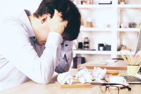 oficina desordenada: Destacó el empresario con la cabeza en las manos sobre el escritorio desordenado