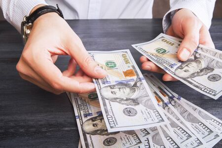 buy: Hands with watch counting dollar bank notes on dark wooden table