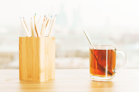 pencil holder: Frontview of table with teacup and wooden pencil holder