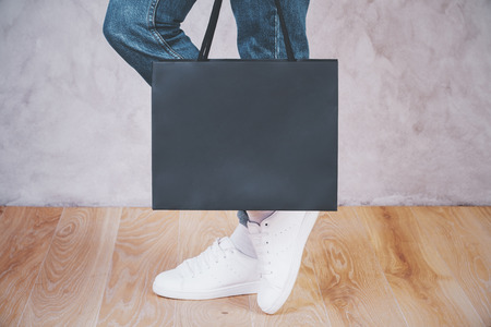 Side view of female feet with shopping bag on concrete background.