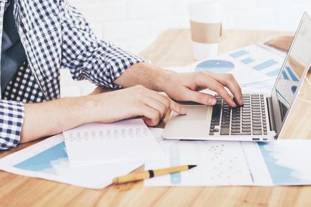 cuadro sinoptico: Lateral de hombre de negocios usando la computadora portátil en el escritorio lleno de hojas de papel con los informes de negocio y taza de café