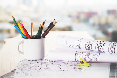 rolled paper: Iron mug with pencils on wooden table with sketches on rolled paper sheets Stock Photo