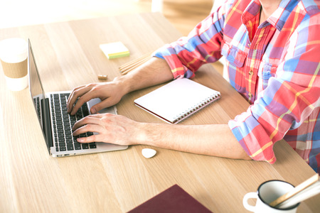 casually: Sideview of businessman using notebook on wooden desk in office