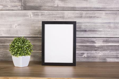 Plant in pot en lege afbeeldingsframe op houten oppervlak. Bespotten Stockfoto