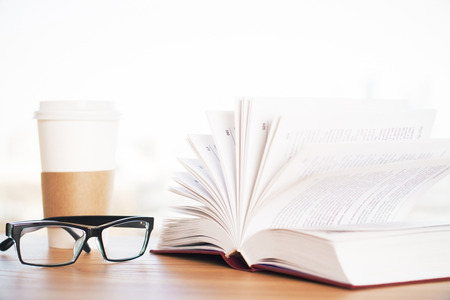 books on a wooden surface: Wooden desk with open book, coffee cup and glasses Stock Photo