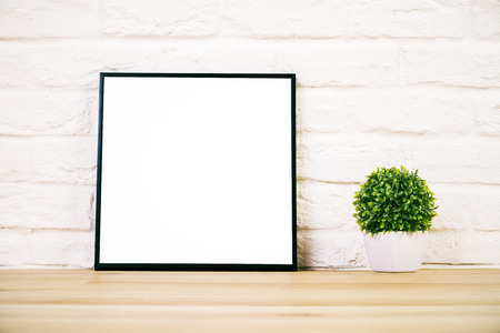 Closeup of wooden surface with blank picture frame and flowerpot on white brick background. Mock up