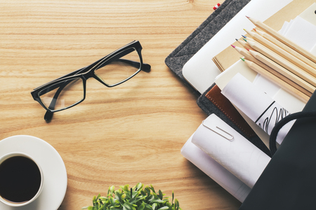 work table: Topview of wooden desk with glasses, coffee, pencils and other items