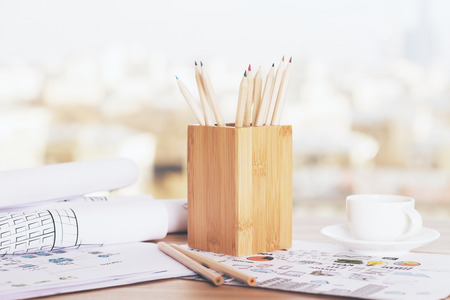pencil holder: Wooden pencil holder and coffee cup on desktop with sketches
