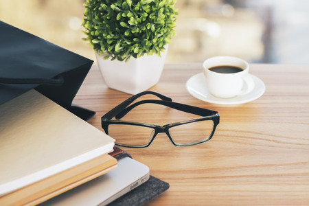 work table: Wooden desktop with glasses, plant, coffee and other items Stock Photo
