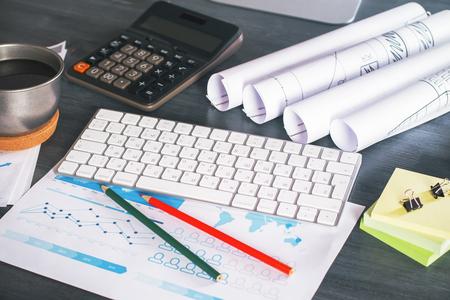 articulos de oficina: escritorio de madera oscura con teclado, calculadora, informe de negocio y otros artículos de oficina Foto de archivo