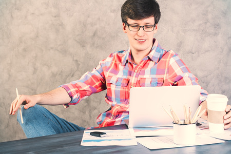 casually: Smiling, casually dressed man looking at laptop placed on office desk with different items Stock Photo