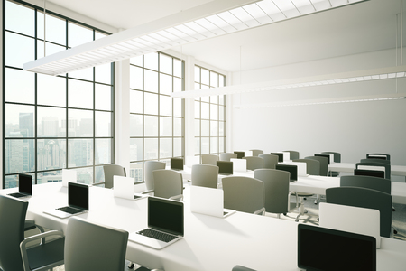 sideview: Sideview of coworking area in office interior with notebooks on tables, ceiling lamps and city view. 3D Rendering