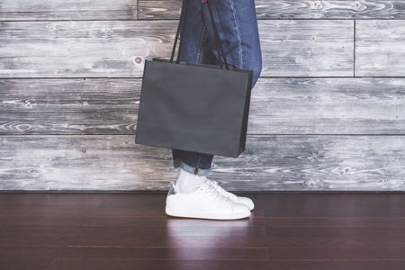 sideview: Sideview of female legs with blank shopping bag on wooden background. Mock up Stock Photo