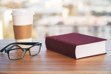 books on a wooden surface: Wooden desk with closed book, coffee cup and glasses Stock Photo