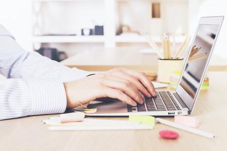 Uomo che utilizza entrambe le mani per digitare sulla tastiera del computer portatile su sfondo sfocato ufficio