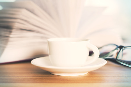 books on a wooden surface: Closeup of wooden table with open book, coffee cup and glasses