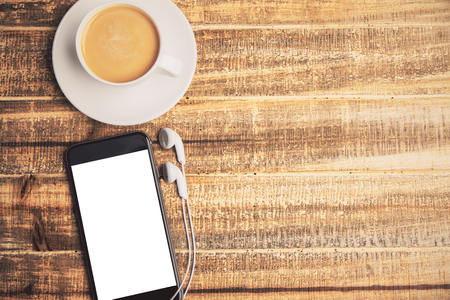 Topview of coffee cup and white phone screen with headphones on wooden table. Mock up