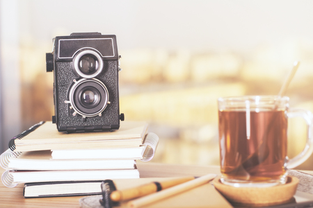 copybook: Wooden desktop with retro camera on copybook stack and cup of tea