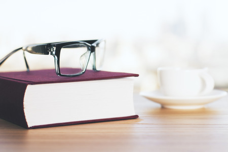 books on a wooden surface: Closed vinous book, coffee cup and glasses on wooden table. Closeup Stock Photo
