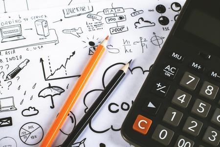 cuadro sinoptico: Dos lápices y calculadora en la superficie con croquis de negocios Foto de archivo