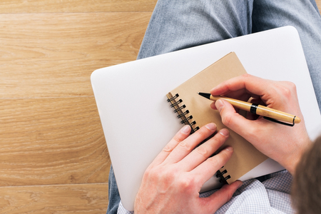 placed: Topview of man writing in aged notepad placed on closed laptop. Wooden background Stock Photo