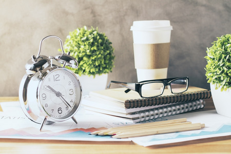 front view: Silver alarm clock, plants, glasses and coffee cup on wooden table
