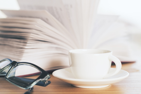 books on a wooden surface: Closeup of wooden desktop with open book, coffee cup and glasses